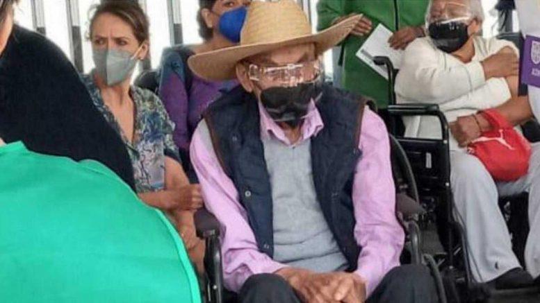 Con lentes de protección y cubrebocas, Luis Echeverría de 99 años, asistió a su cita en silla de ruedas.